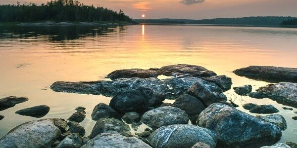 Ondergaande zon bij een waterlijn met rotsstenen